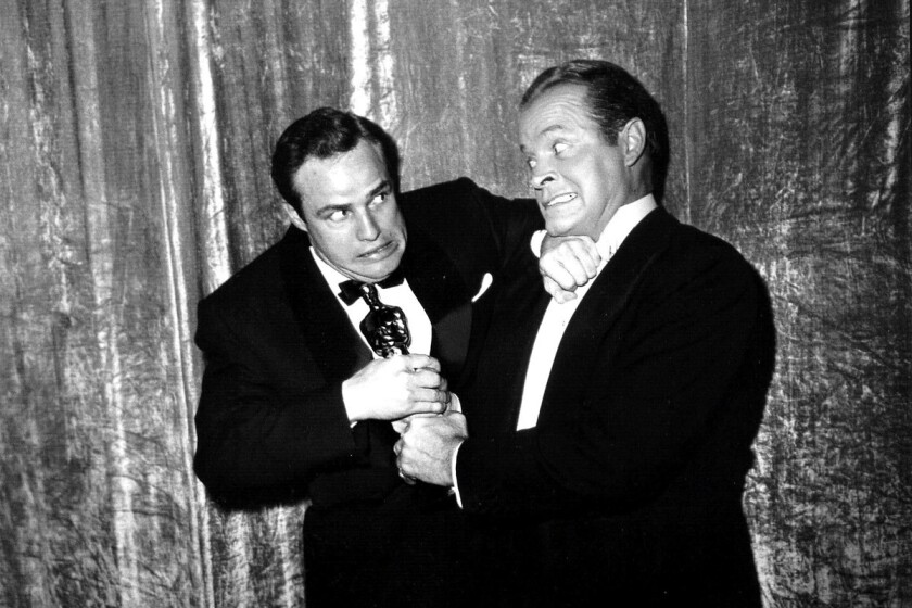 """Marlon Brando, left, in a mock 'fight' with Bob Hope over his Oscar for """"On the Waterfront"""" in 1951. Hope, who hosted the Oscars in 1940, was the first to bring comedy into the ceremony's proceedings."""