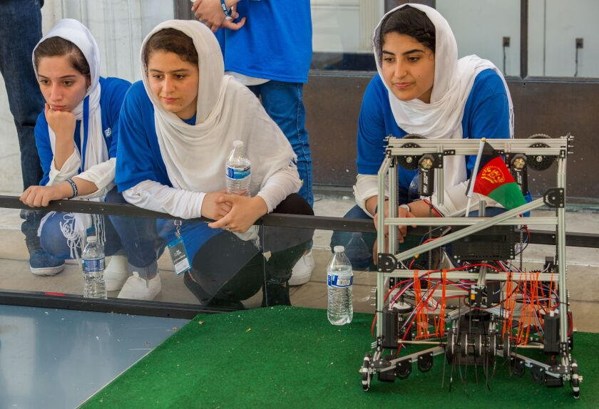 Members of Afghan all-female robotics team kneel on the floor next to their robot