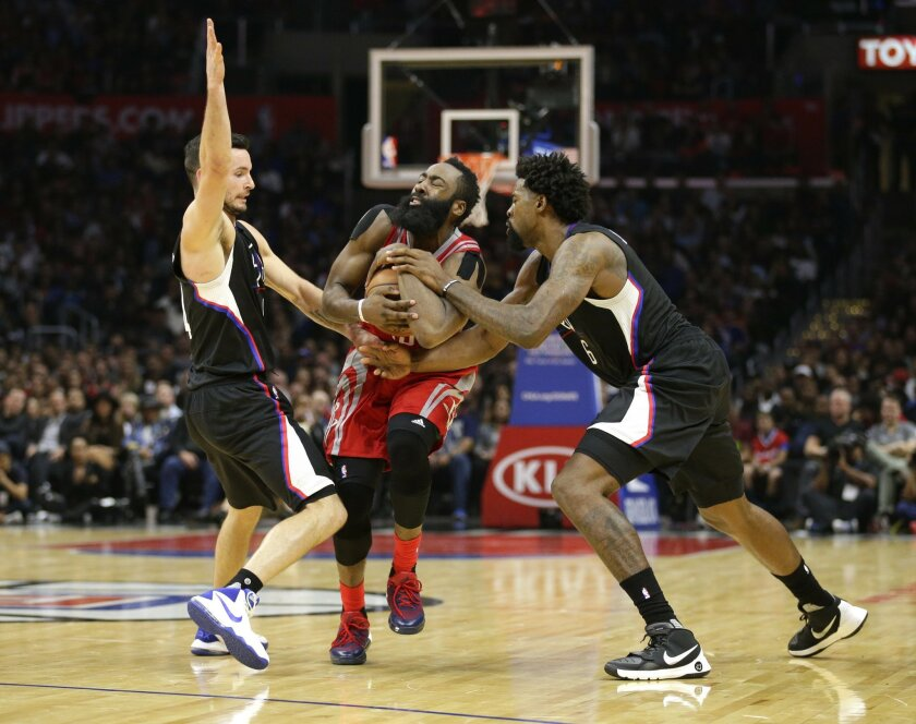 Houston Rockets' James Harden, center, is defended by Los Angeles Clippers' J.J. Redick, left, and DeAndre Jordan during the second half of an NBA basketball game, Saturday, Nov. 7, 2015, in Los Angeles. The Rockets won 109-105. (AP Photo/Jae C. Hong)