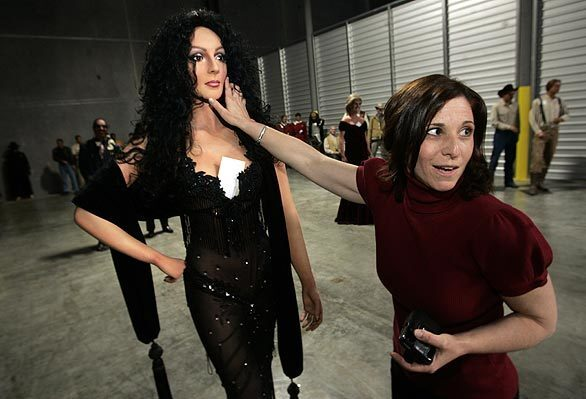 Aileen Stein checks out a wax figure of Cher, which is among more than 200 hand-sculpted statues that will be sold by the Hollywood Wax Museum as it modernizes. The life-size replicas made of oil-painted wax are at a Newbury Park warehouse.