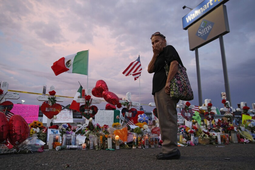 FILE - In this Aug. 6, 2019 file photo, Catalina Saenz wipes tears from her face as she visits a makeshift memorial near the scene of a mass shooting at a shopping complex in El Paso, Texas. El Paso is marking the year anniversary of the a shooting at a crowded Walmart by remembering the 23 people killed. Authorities have said the gunman traveled from his home near Dallas to target Latinos in the Texas border city on Aug. 3, 2019. (AP Photo/John Locher, File)