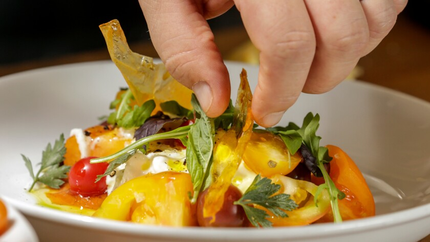 Chef Bruce Kalman, prepares Caprese Salad, made with dehydrated roasted tomato skin chips, at Union Restaurant in Pasadena.