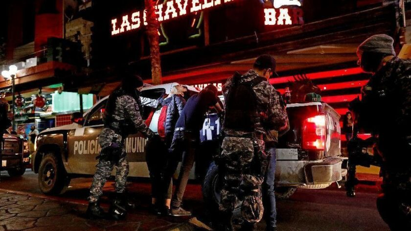 Officers from a specialized Tijuana police unit frisk people for drugs and firearms in red light district of the city's Zona Norte on Dec. 10.