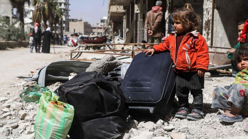 A Syrian child stands next to luggage with other civilians as they wait to be evacuated from the town of Arbin in the eastern Ghouta region on the outskirts of the capital Damascus.