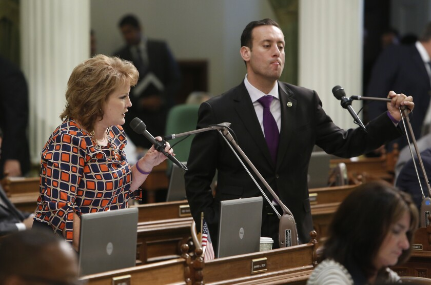 In this 2013 photo, Assemblyman Roger Hernandez (D-West Covina) listens as Assemblywoman Shannon Grove (R-Bakersfield) urges lawmakers to reject a bill Hernandez was carrying at the Capitol in Sacramento.