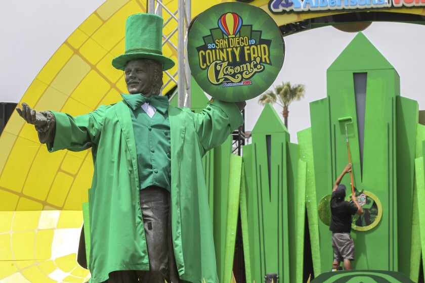 With the Don Diego statue dressed as the Wizard of Oz in the foreground, Andy Mazon paints a depiction of the Emerald City at the front entrance of the San Diego County Fair on Thursday in Del Mar. The fair opens Friday.