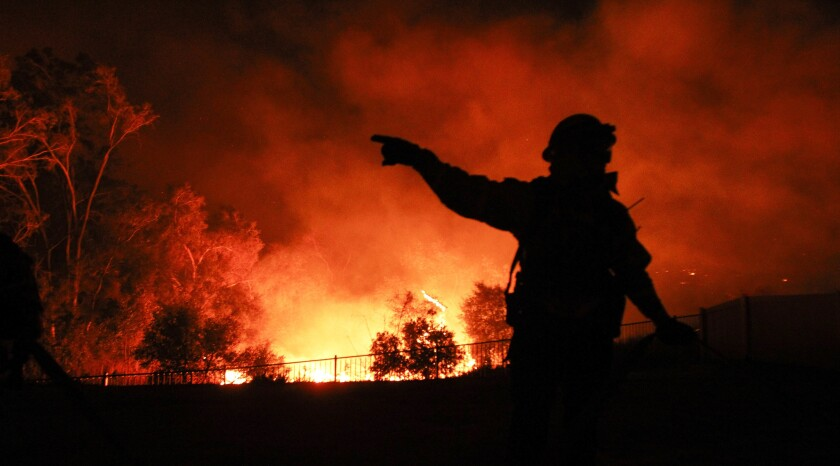 A San Diego Fire and Rescue firefighter gestures to another as they protect a home from the Lilac Fire in Bonsall in December 2017.