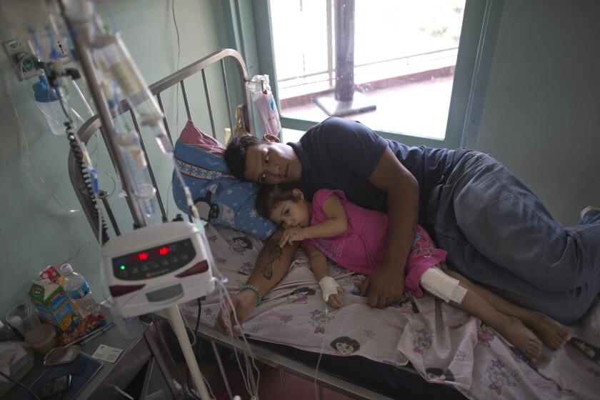 En esta imagen, Maykol Pacheco se acurruca con su hija Ashley en su cama de hospital, durante su estancia de dos meses en el Hospital Universitario de Caracas, en Venezuela. (AP Foto/Ariana Cubillos)
