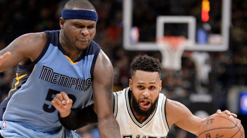 San Antonio Spurs guard Patty Mills, right, drives against Memphis Grizzlies forward Zach Randolph d