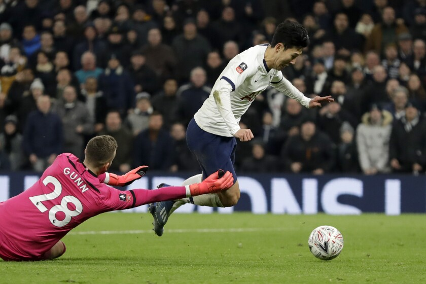 Southampton's goalkeeper Angus Gunn fouls Tottenham's Son Heung-min, right, in the box to give away a penalty shot during the English FA Cup fourth round replay soccer match between Tottenham Hotspur and Southampton at the Tottenham Hotspur Stadium in London, Wednesday, Feb. 5, 2020. (AP Photo/Kirsty Wigglesworth)