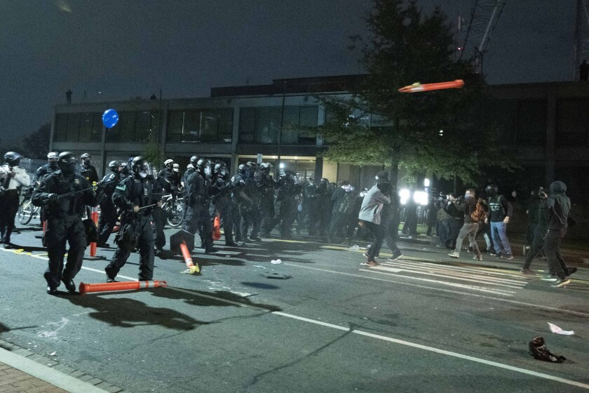 Washington Metropolitan Police Department police officers push back demonstrators outside of the fourth district police station in Washington, Wednesday, Oct. 28, 2020. Demonstrators gathered at the police station in protest over a fatal a crash involving a moped driver who died when he police were attempting to pull him over. The crash happened last Friday. (AP Photo/Jose Luis Magana)