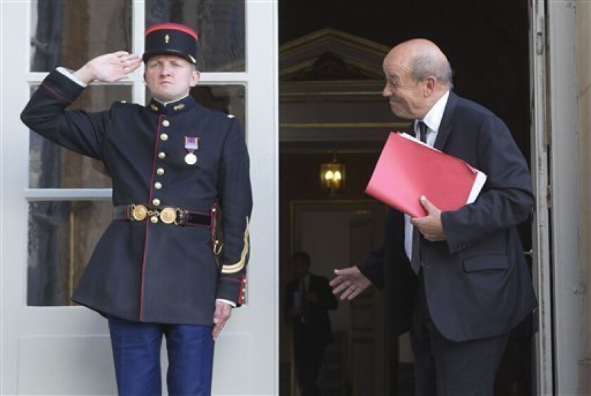 French Defense Minister Jean-Yves Le Drian, right, reacts as he arrives at the French Prime Minister in Paris, Monday Sept. 2, 2013. French Prime Minister Jean-Marc Ayrault will meet with the leaders of Parliament's defense and foreign affairs committees. The prime minister's office said Ayrault will give the lawmakers an update on Syria and show them a declassified report on Syria's chemical weapons to back up France's claim that the Assad regime was responsible for the attack. (AP Photo/Michel