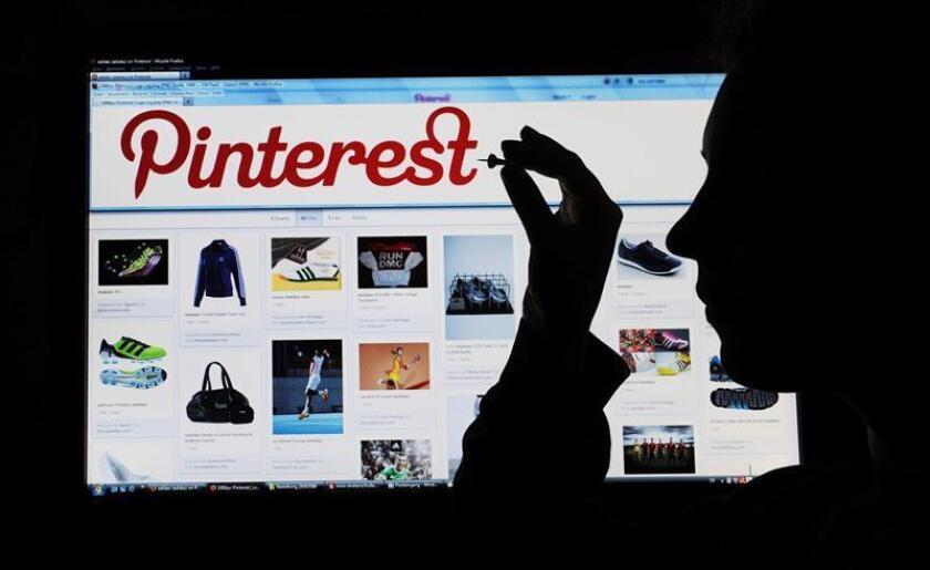 Una ilustración de fecha 23 de marzo de 2012 muestra a una mujer sosteniendo un alfiler en una pantalla de computadora que muestra el sitio web de la red de intercambio de fotos Pinterest en Hanover, Alemania. EFE/Archivo