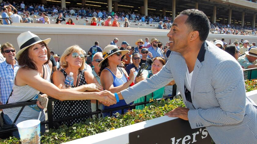 Former Chargers player Terrell Fletcher shakes hands with a fan at the Del Mar race track on Saturday.