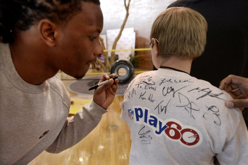 NFL prospect Kevin White, of West Virgina, left, signs an autograph for pediatric patient Evan Schaumburg during the NFL PLAY 60 activities at Shriners Hospital for Children Thursday, April 30, 2015, in Chicago. (AP Photo/Paul Beaty)