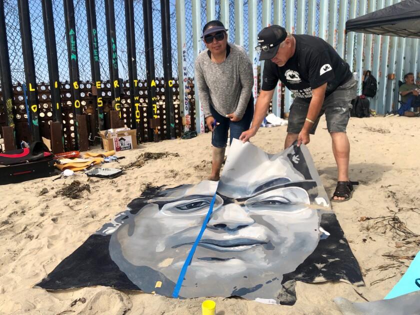 Montserrat Godoy (i), ayuda a cortar los trazos de su rostro que será plasmado en el mural en Playas de Tijuana como parte del proyecto Who Are the Real Childhood Arrivals to the United States?