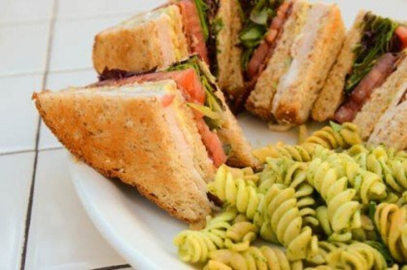 The Turf Club stacks turkey, bacon, avocado, lettuce, tomato and ranch dressing on three pieces of toast with a side of homemade cilantro pasta salad.