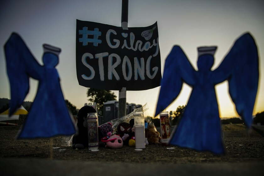Mourners leave items at a roadside memorial in Gilroy, Calif., after a mass shooting at the Gilroy Garlic Festival last year.