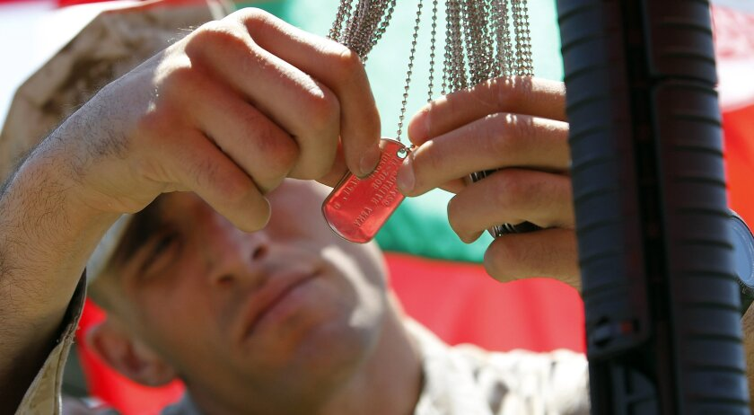 Marine Sgt. Nicholas Ibis gathers military tags from a battle cross after a memorial service at Camp Pendleton for international forces killed in southwestern Afghanistan in the last year.