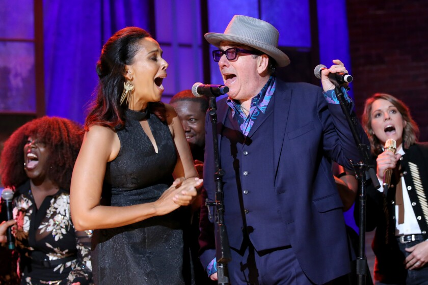 Rihannon Giddens and Elvis Costello singing into one microphone with Brandi Carlile and others singing behind them.