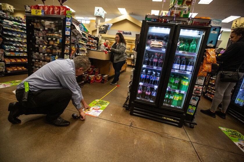 A worker measures the floor at a grocery checkout lane