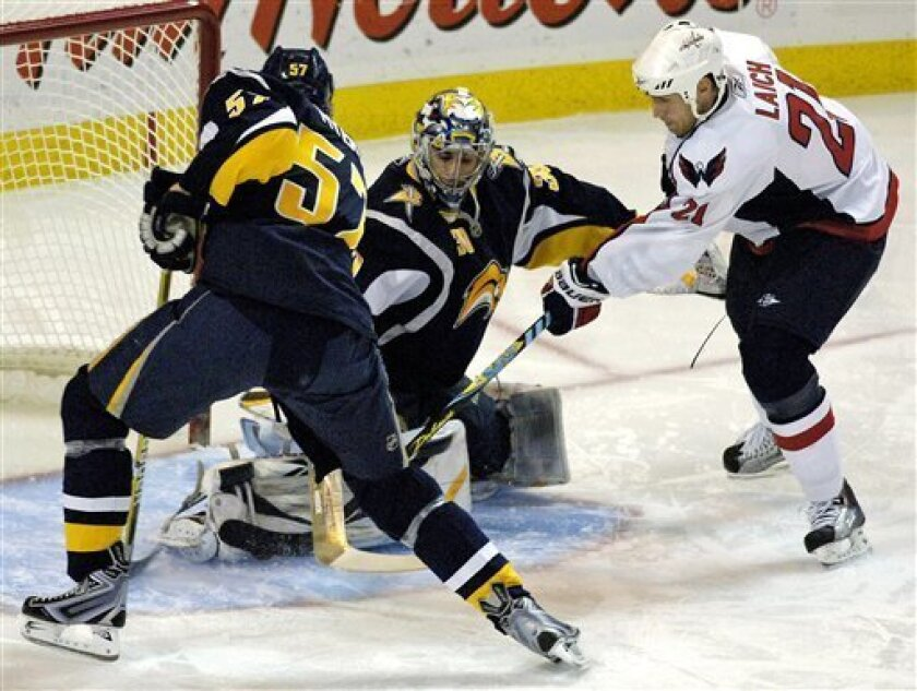 Buffalo Sabres goalie Ryan Miller, center, makes a save on Washington Capitals center Brooks Laich, right, as Sabres defenseman Tyler Myers assists on the play during the first period of the NHL hockey game in Buffalo, N.Y., Wednesday, Dec. 9, 2009. (AP Photo/Don Heupel)
