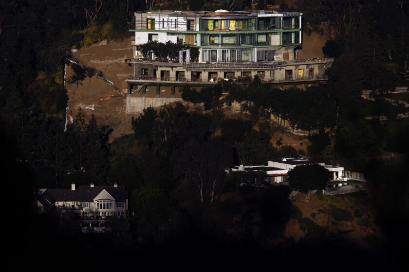 BEL AIR, CA - MAY 23, 2017 - The unfinished mansion at 901 Strada Vecchia Road towers over a pair of