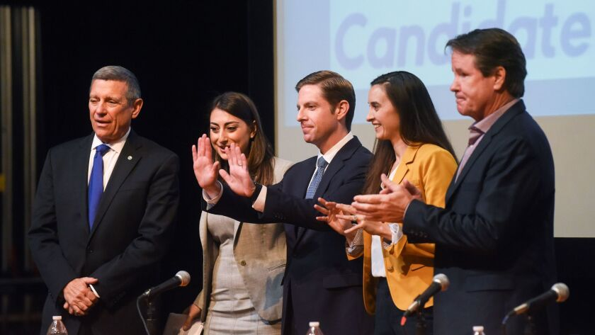 Mike Levin, center, waves to his supporters onstage with the other Democratic candidate for the 49th