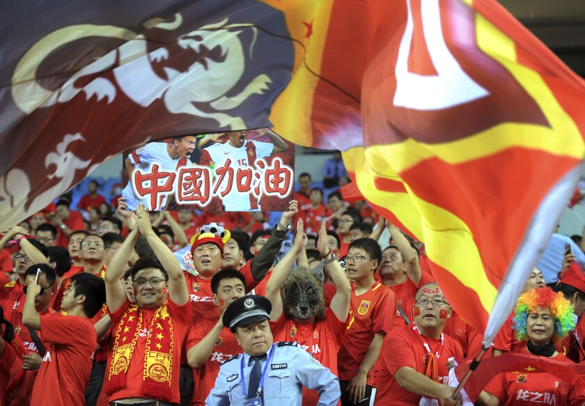 A policeman looks on as Chinese soccer fans cheer during the 2018 World Cup qualifying soccer match between China and Iran held in Shenyang in northeast China's Liaoning province, Tuesday, Sept. 6, 2016. (Color China Photo via AP)