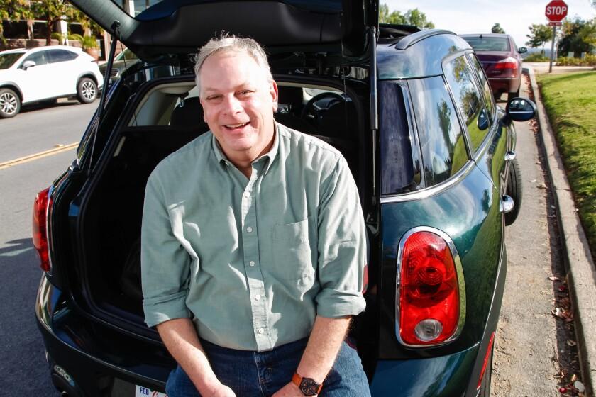 "Jack Brandais, author of ""Joyrides Around San Diego,"" stands with his car along Avenida de Acacias in Rancho Santa Fe."