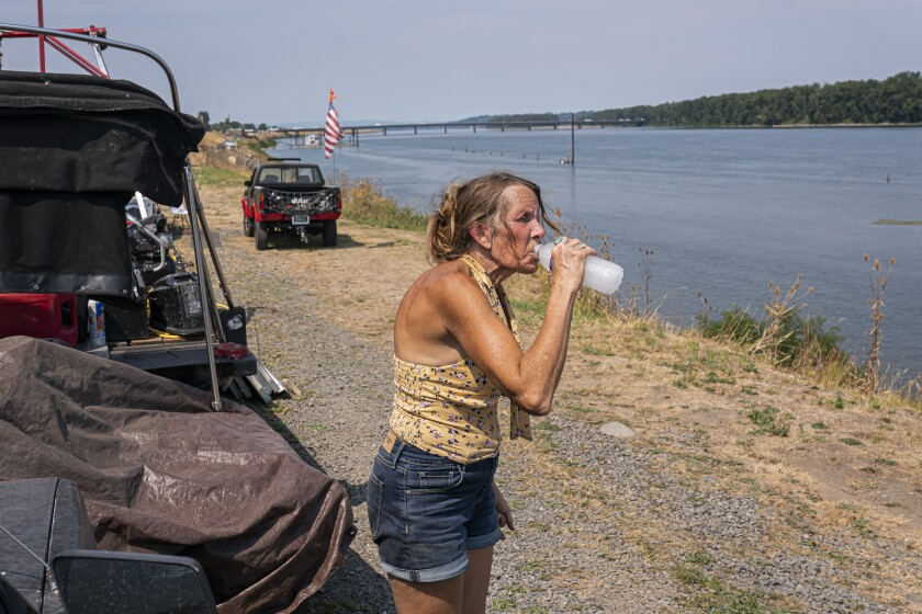 A woman living along the Columbia River who declined to be named, drinks a bottle of water delivered by Cascadia Behavioral Healthcare's street outreach team on Thursday, Aug. 12, 2021, in Portland, Ore. (AP Photo/Nathan Howard)