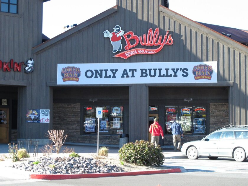 Visitors to a shopping strip mall in north Sparks walk Wednesday, (Feb. 25, 2015, in front of a Bully's Sports Bar & Grill _ one of seven that make up the largest chain of sports bars in northern Nevada. A federal lawsuit filed in U.S. District Court in Reno accuses Bully's of violating U.S. labor