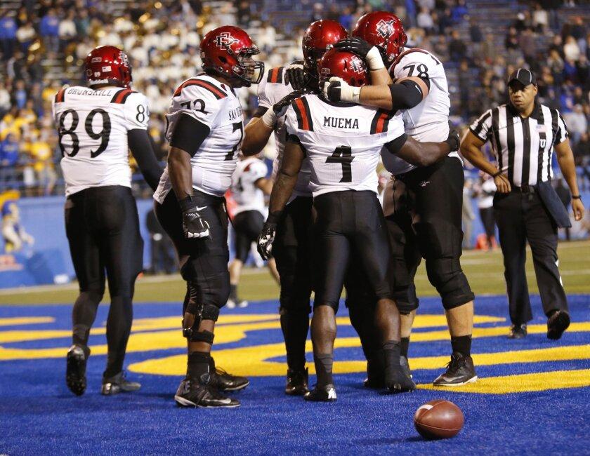 The Aztecs celebrate Adam Muema's game-winning touchdown that beat the Spartans 34-30 in San Jose Saturday night.