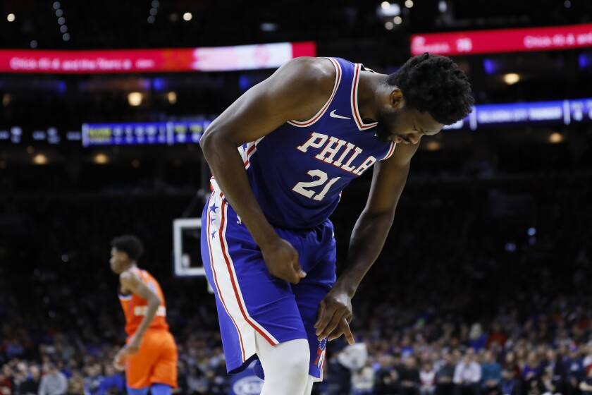 Philadelphia center Joel Embiid writhes in pain after injuring his left ring finger during a game Jan. 6, 2020.