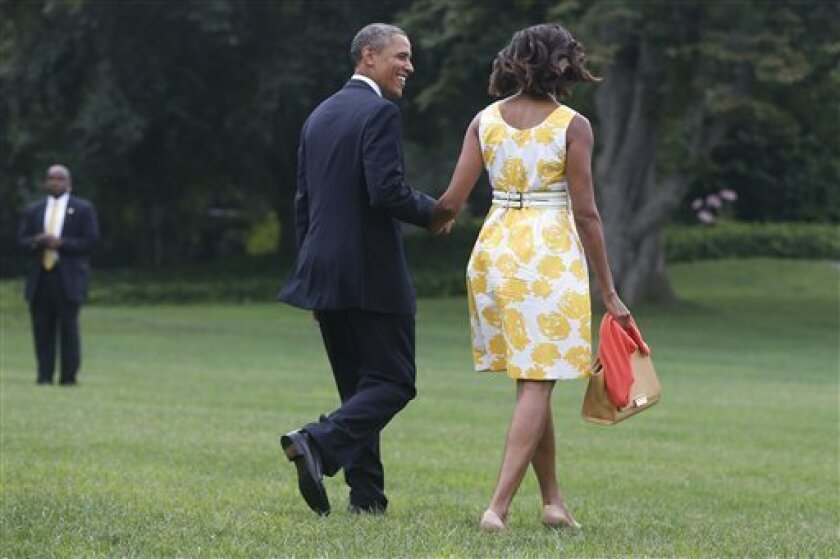President Barack Obama and first lady Michelle Obama walk on the South Lawn at the White House in Washington, Saturday, Aug. 10, 2013, as they travel to Orlando, Fla. before heading to their vacation in Martha's Vineyard. (AP Photo/Charles Dharapak)