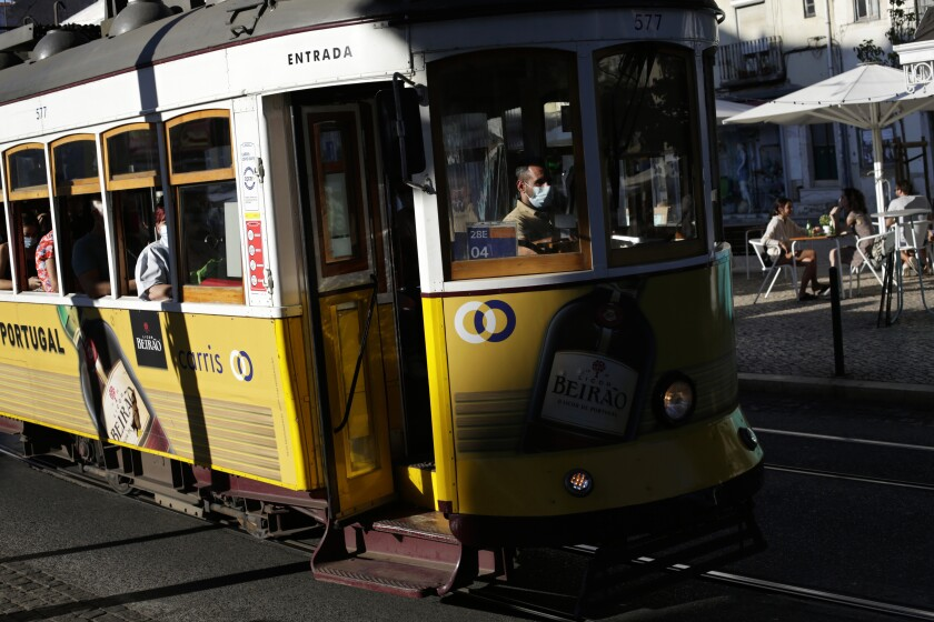 A tram conductor wearing a face mask drives through Lisbon's Graca neighborhood, Monday, July 26, 2021. The head of Portugal's vaccine rollout program says the country is experiencing steep shortfalls in expected deliveries of the Janssen COVID-19 jab. In August, only 200,000 Janssen doses will be delivered instead of the expected 600,000. (AP Photo/Armando Franca)