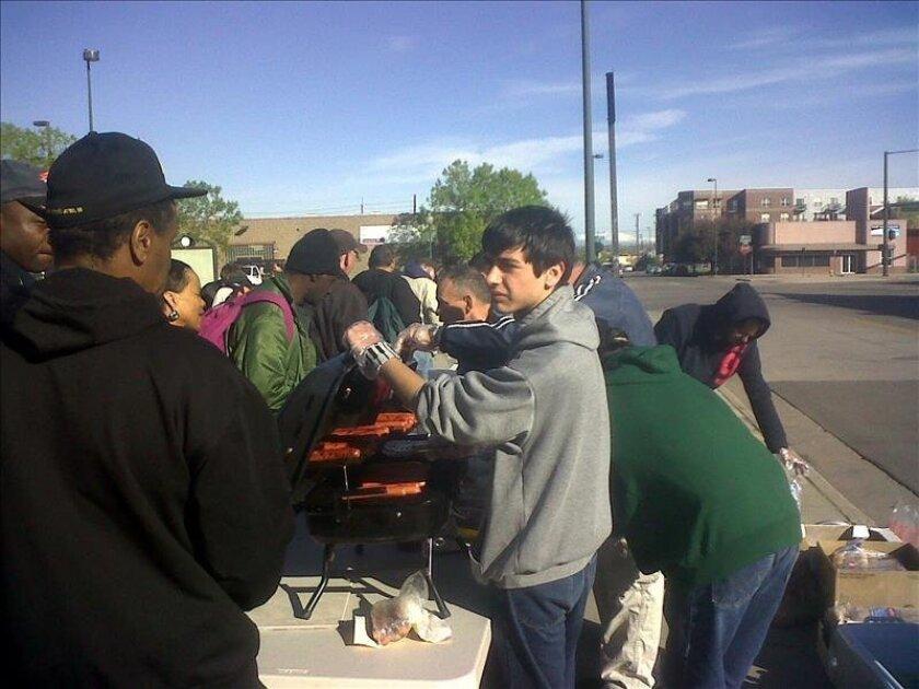 Unos desamparados reciben alimentos en la plazoleta de la esquina de Broadway y Lawrence, en el centro de Denver, Colorado. EFE/Archivo