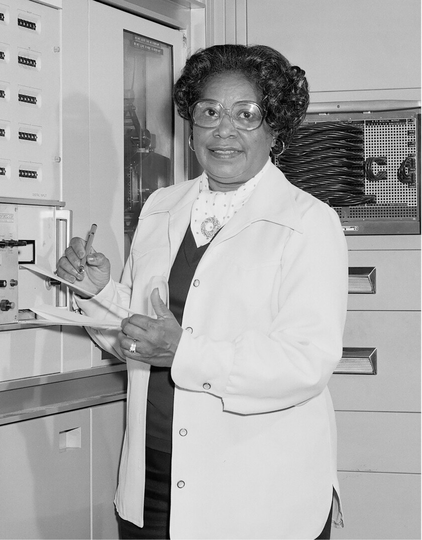Mary W. Jackson stands in a white coat holding a clipboard.