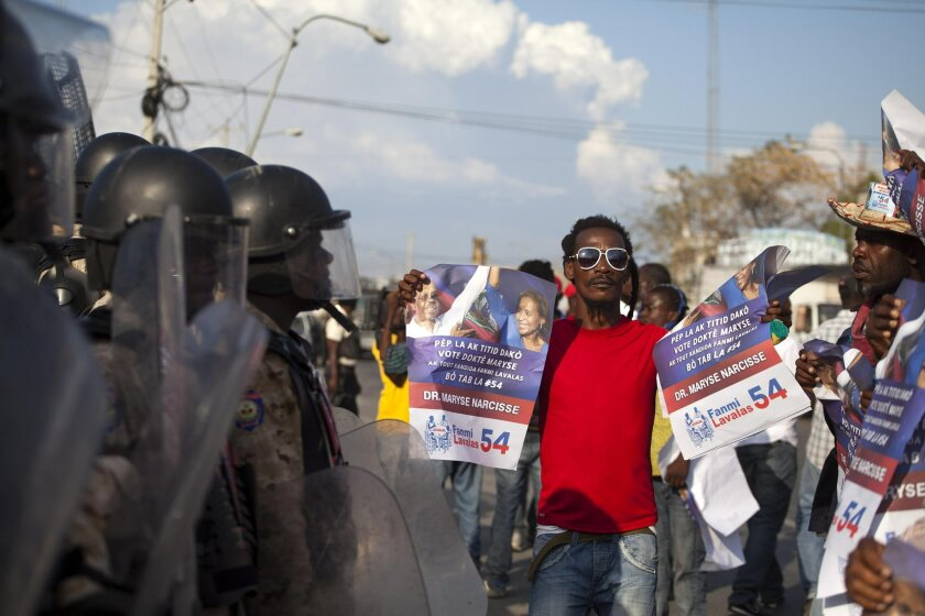 A demonstrator holds pictures of ousted President Jean Bertrand-Aristide with former presidential candidate Maryse Narcisse during a march in favor of Senate President Jocelerme Privert for interim president, outside Parliament in Port-au-Prince, Haiti, Saturday, Feb. 13, 2016. Supporters of Bertra