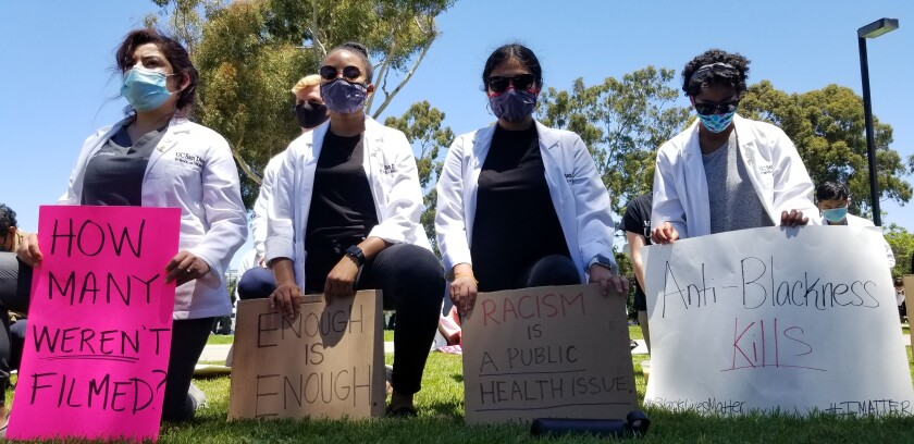 Four medical students kneel and hold anti-racism signs.