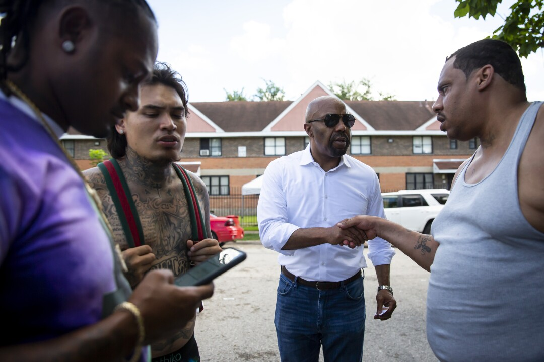 Daryl Washington, center, speaks with community members of Houston's Third Ward.