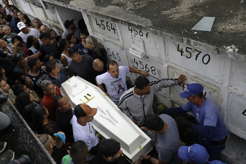 FILE - In this Sept. 22, 2019 file photo, People carry the coffin of Ágatha Sales Felix, who was hit by a a stray bullet, at a cemetery in Rio de Janeiro, Brazil. Police announced on Tuesday, Nov. 19, that it was an officer that fired the shot that killed the 8-year-old girl. (AP Photo/Silvia Izquierdo, File)
