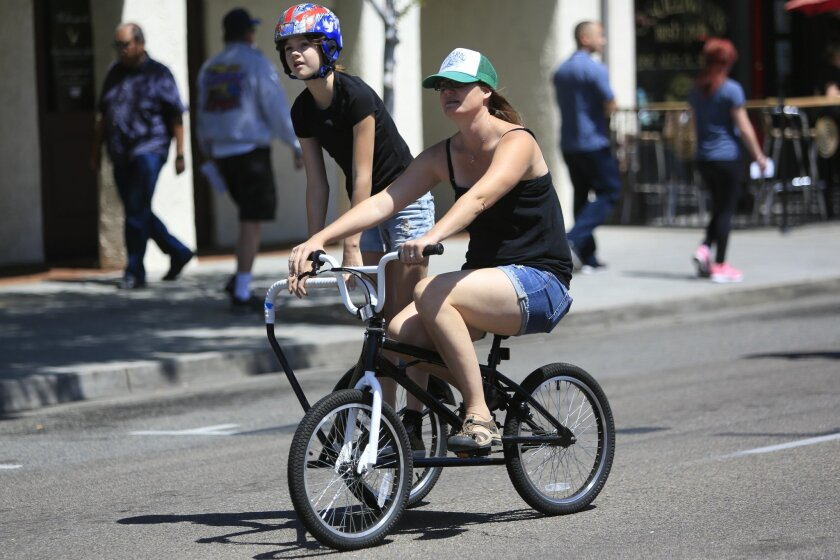 Jo-Ann Fox pedals down Grand Avenue in Escondido with her daughter, Shasta on a side-hack bike during the Cicliovia event on Saturday.