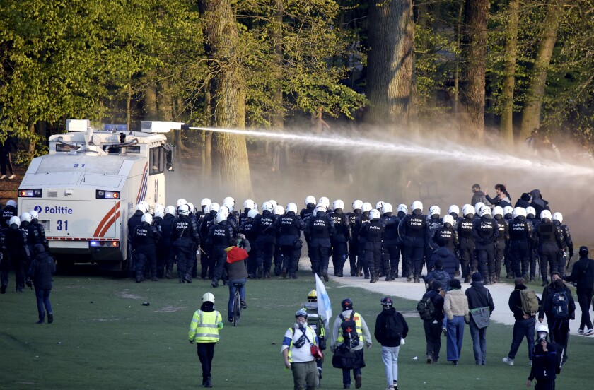 """Police use a water cannon against protestors at the Bois de la Cambre park during a party called """"La Boum 2"""" in Brussels, Saturday, May 1, 2021. A few thousand people gathered for an illegal party in a Brussels park Saturday to protest COVID-19 restrictions, only to be met with a big police force who used a water cannon and tear gas to disperse the crowd. It was the second such open-air gathering in a month. (AP Photo/Olivier Matthys)"""