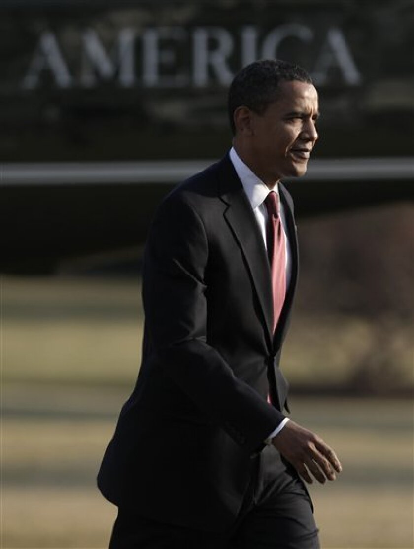 President Barack Obama arrives on the South Lawn of the White House in Washington, Monday, Feb. 9, 2009, after a day trip to Elkhart, Ind. (AP Photo/Evan Vucci)