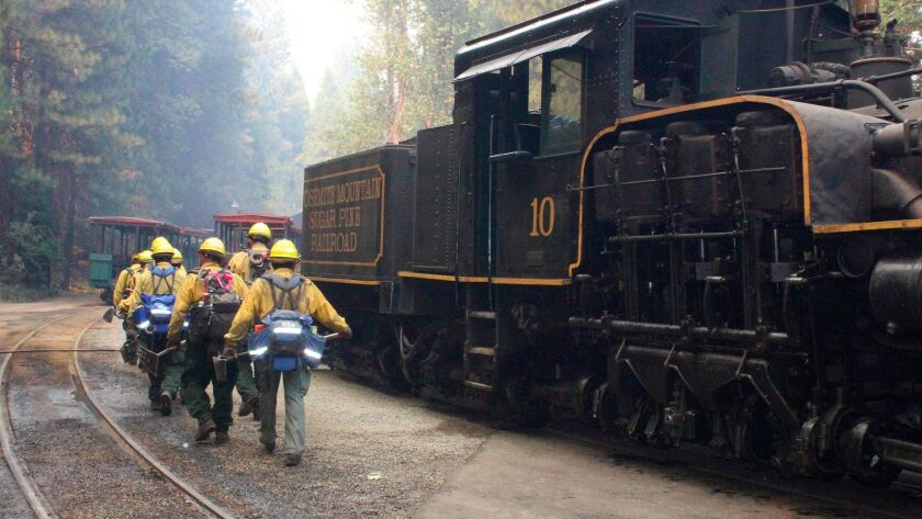 In this Tuesday, Aug. 29, 2017 photo, U.S. Forest Service hand crew out of Fresno, Calif., walks tow