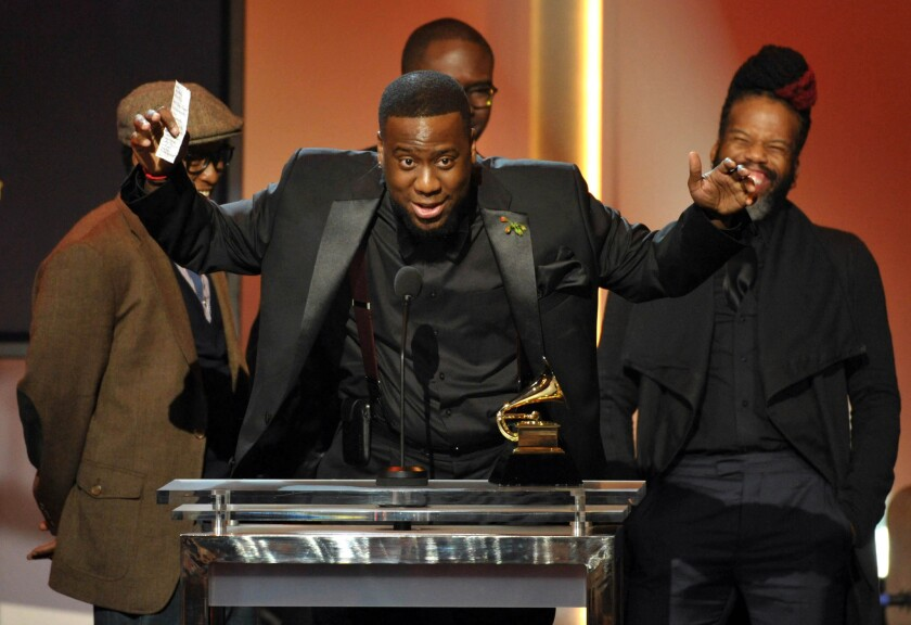 "Robert Glasper, center, accepts the award for R&B; album for ""Black Radio"" during the Grammy Awards' pre-telecast Sunday in Los Angeles."