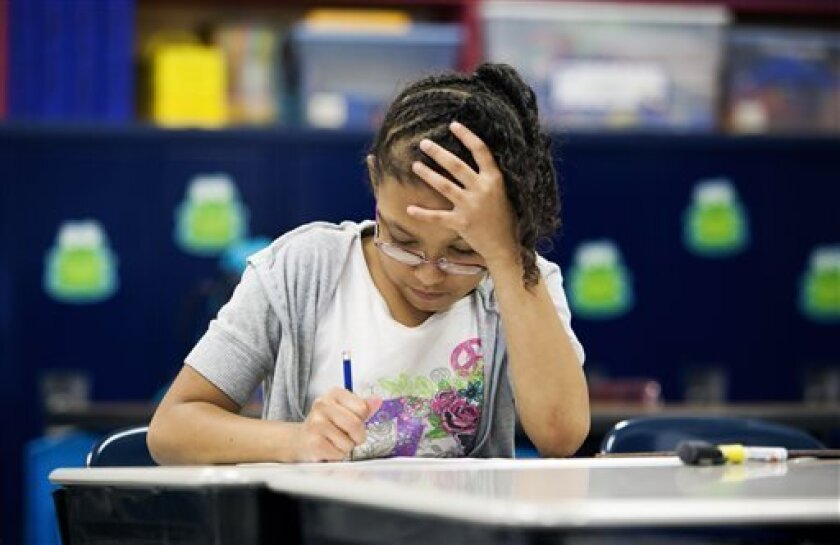 Shaevon Boyd, a third grader at Southside K-8 School in War, W.Va., works on a reading assignment during an after school program on Tuesday, May 7, 2013. The school located in McDowell County, an area overwhelmed with poverty, unemployment, drug abuse, and teacher shortages, provides after school access to computers, tutoring, recreation and a meal. McDowell County on Wednesday was expected to win approval to expand its role to include social services in a county that faces deep economic challen