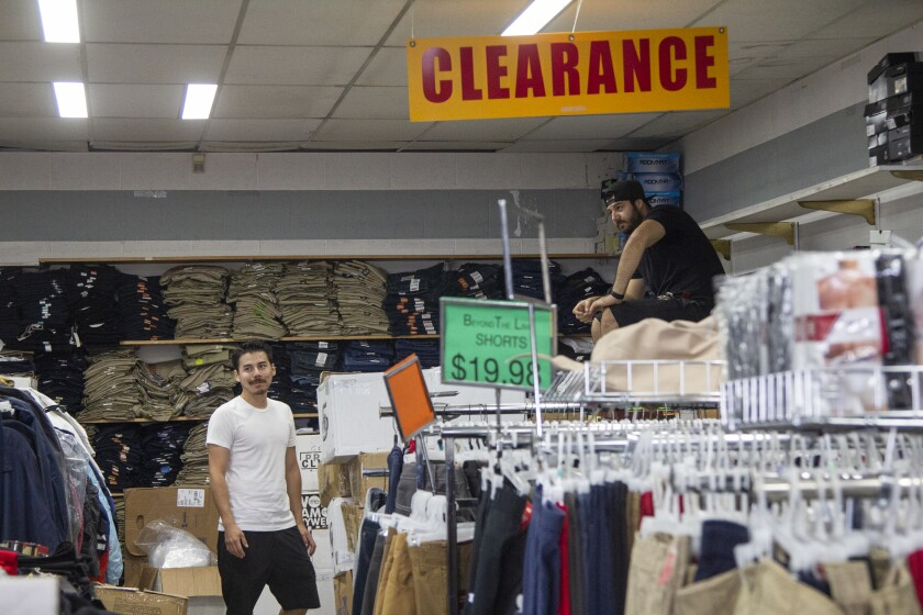 Mario DeAnda's sons Marc and Michael pack up clothes for the store's closure.