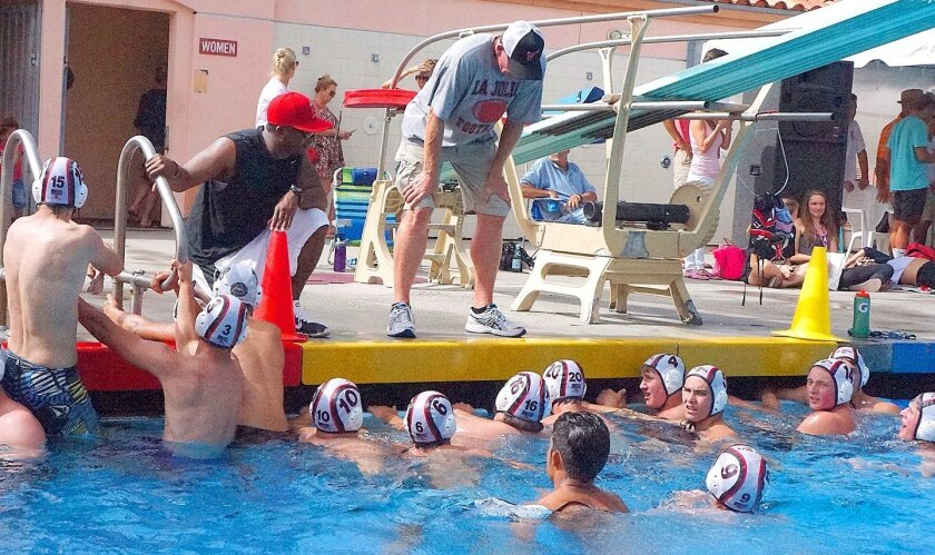 La Jolla High School's head football coach Jason Carter and assistant coach John McColl strategize with players during the Tangle in the Tank match to benefit Susan G. Komen San Diego Foundation at the school's Coggan Family Aquatic Complex, Oct. 14, 2015.